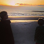 Boys admiring beach sunset